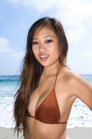 A beautiful Asian woman at the beach wearing her bikini Stock Photo - 7443129