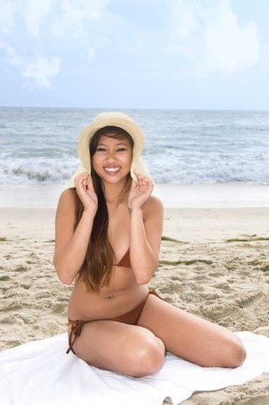 A young Asian woman relaxing at the beach wears a hat to help protect from the sun. Stock Photo - 7443084