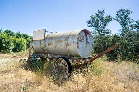 An antiquated horse drawn water cart in a rural area during the daytime. Stock Photo - 7443956