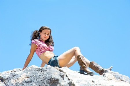 A sexy woman with short shorts and piggy tails sits on a mountaintop. photo