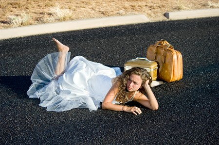 A bride is kicked to the curb and all alone along an isolated street. photo