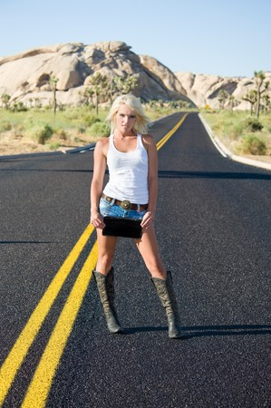 A beautiful model standing in the middle of a remote desert road holds a blank license plate for copy.  Good for travel inferences. photo