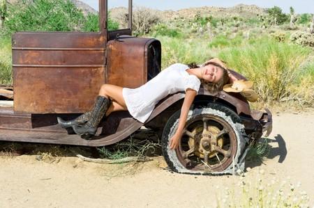 国の女の子、リモート砂漠で古い車のフェンダーに休憩します。 写真素材
