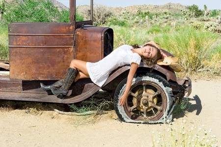 A country girl resting on the fender of an old car in a remote desert. photo