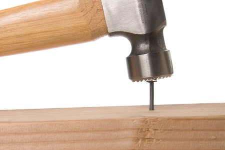hammer head: A nail is being hammered into place during a construction project.  The image can be used for any tooling, fabrication or construction inference. Stock Photo