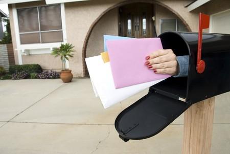 A hand reaches through a mail box to grasp letters. photo