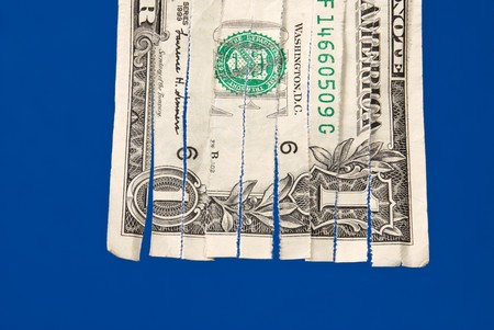 inferences: A shredded dollar bill isolated on blue.  The image can be used for economic financial inferences. Stock Photo