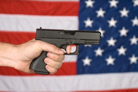 violence and trigger: A man displays his semi automatic pistol against an American flag.
