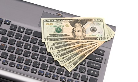 Cash lying on a keyboard during an online Internet shopping spree. photo