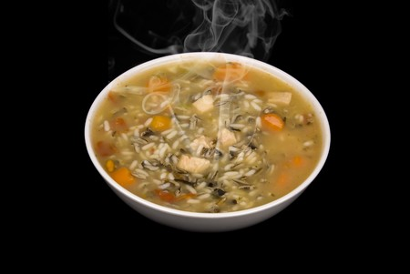 A bowl of piping hot chicken and rice soup isolated on a black background.
