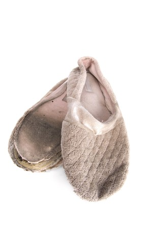 A pair of old, ratty house slippers on a white background