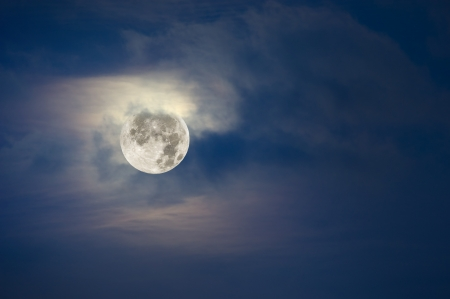 moon light: A brightly lit full moon lights up the clooudy, hazy sky.