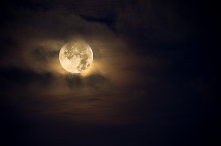 A dark night brings a bright, amber moon alive with puffy hazy clouds.