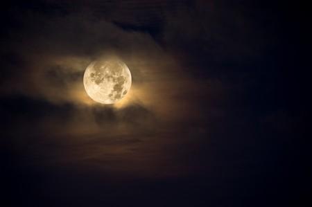 brings: Una notte oscura porta una luna luminosa, ambra viva con puffy nuvole nebuloso.