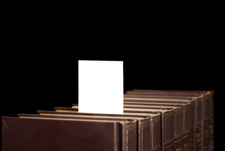 A row of books holds a message card for designers to place copy. 版權商用圖片 - 7443791