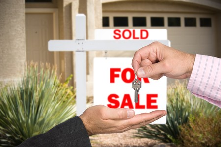 A realator hands over the keys to a new home buyer after the sale is final. Stock Photo