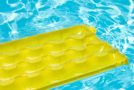 A yellow raft drifts in a swimming pool.