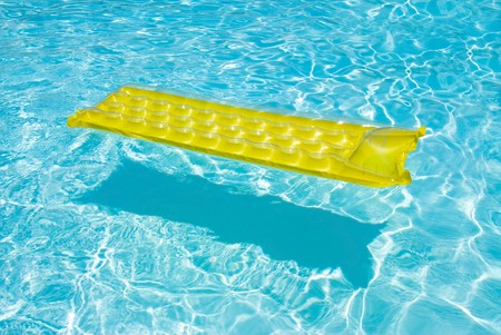 float tube: A yellow raft floats in a swimming pool. Stock Photo