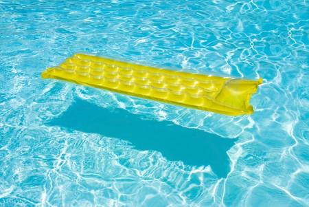 jangada: Una balsa amarilla flota en una piscina.  Foto de archivo