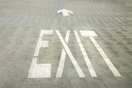 way out: An exit sign painted on a concrete parking lot shows the way out.