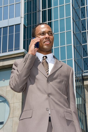 equal opportunity: A businessman walks through a business park talking on his cell phone.