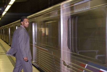 A business traveler waits for a passing subway train to stop. photo