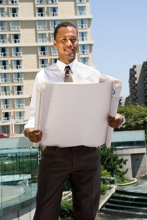 A male Africian American architect executive reviews specifications for a project.