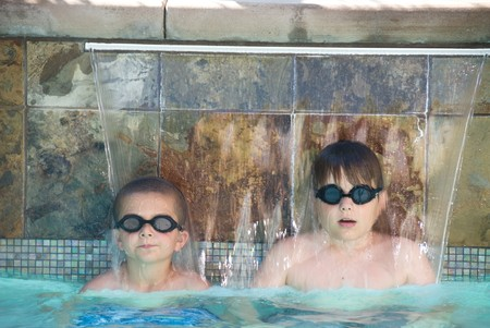 Children enjoys the summer by cooling off in a swimming pool. photo
