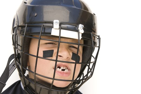 A young boy shows off his missing teeth while in his hockey gear. photo