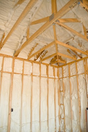 rafter: A room at a newly constructed home is sprayed with liquid insulating foam before the drywall is added.  Ideal for new home construction advertising and other home construction promotional inferences.
