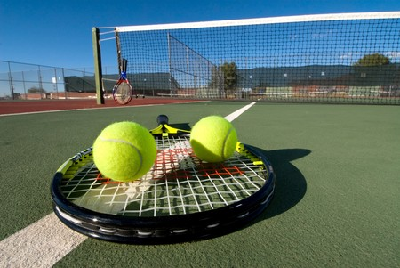 An image depicting the concept of tennis, including the court, racquets, balls and blue outdoors. photo