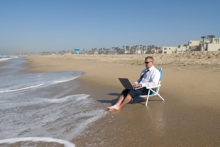 A businessman takes his office to the beach. Imagens