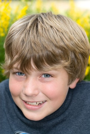 9 year old: A 9 year old boy smiles while resting in a field of yellow sprintime flowers Stock Photo