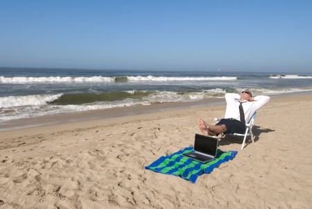 takes: A businessman takes his office to the beach. Stock Photo