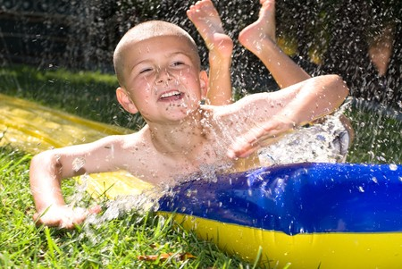 A kid slides down a slippery water slider during a hot summer day. Stock Photo