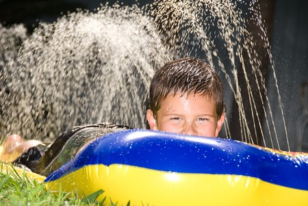A kid slides down a slippery water slider during a hot summer day. photo