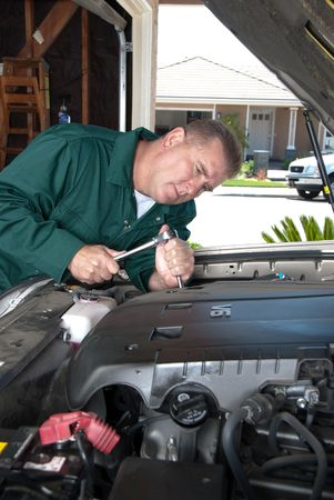 An auto mechanic uses a socket wrench to conduct maintenance and repair a car engine. photo