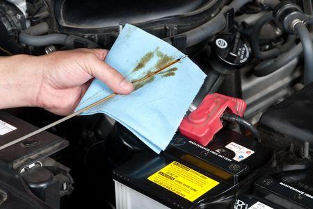 Een automonteur controleert het oliepeil in de motor van een auto tijdens een routine-onderhoud.