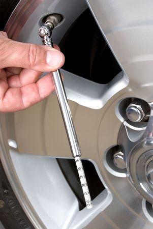 人はタイヤのゲージで、タイヤの空気圧をチェックします。これは責任がある車メンテナンス推論良いイメージです。 写真素材