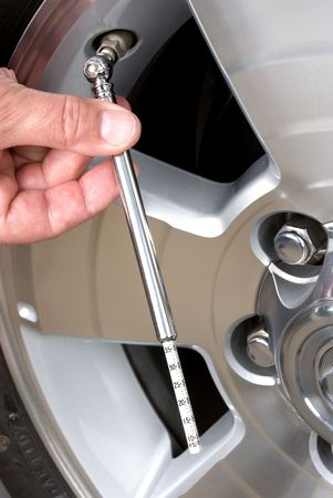 Person checks their tire pressure with a tire guage.  This is a good image for responsible car maintenance inferences.