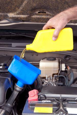 Een monteur giet verse olie in een motor van de auto als onderdeel van het onderhoud. Stockfoto