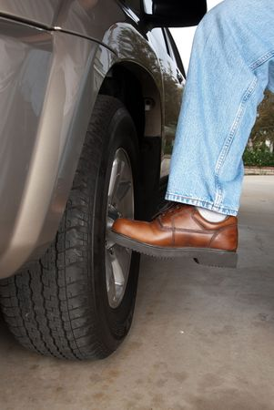 tire: A man kicks his car tire to make sure its inflated and and secured properly.