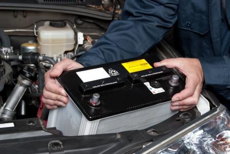 bater�a: Un mec�nico de autom�vil reemplaza una bater�a.  Foto de archivo