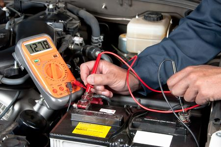 An auto mechanic uses a multimeter voltmeter to check the voltage level in a car battery. Imagens