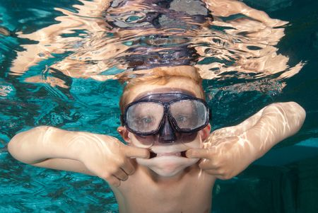 A young boy makes a face underwater while swimming during summer break.  Stock Photo