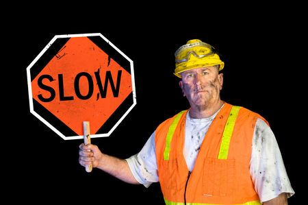 greasy: A dirty, greasy utility construction worker with a yellow hard hat, safety goggles, and a reflective orange vest holding up a warning slow sign.