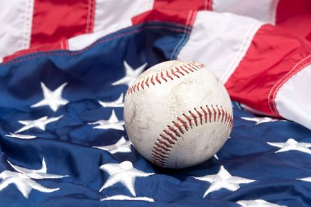 A scuffed up baseball on an American flag.