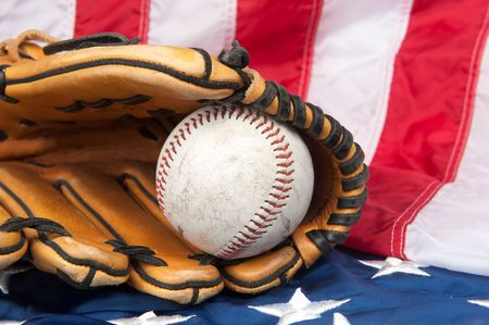 A baseball glove and baseball on an American flag. Stock Photo - 7909513