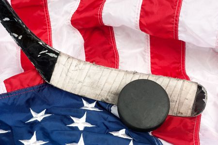 equipment: Hockey equipment including a stick and puck on an American flag to infer a patriotic American sport. Stock Photo