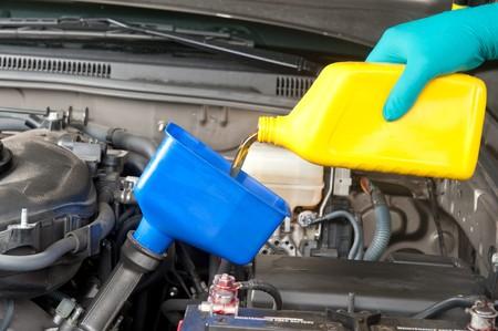 mecanico automotriz: Un mec�nico automotriz cambia el aceite en un autom�vil moderno.  Foto de archivo